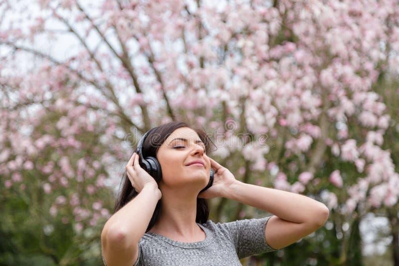 Jovem mulher que escuta a m?sica em fones de ouvido sem fio em um parque com ?rvores da flor de cerejeira fotografia de stock royalty free