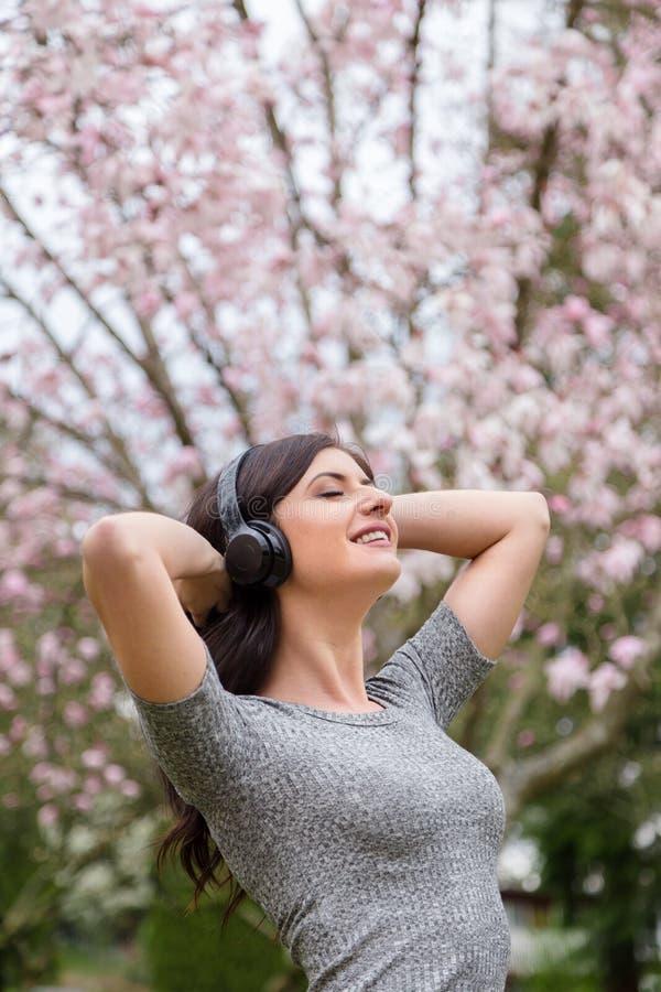 Jovem mulher que escuta a m?sica em fones de ouvido sem fio em um parque com ?rvores da flor de cerejeira fotografia de stock