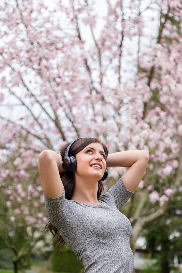 Jovem mulher que escuta a m?sica em fones de ouvido sem fio em um parque com ?rvores da flor de cerejeira foto de stock royalty free
