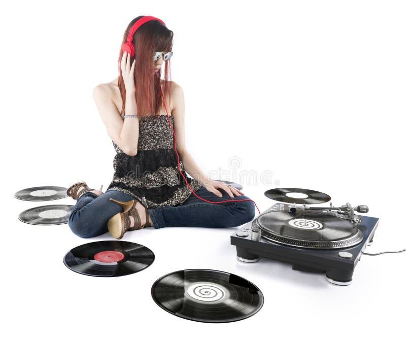 Jovem mulher que escuta uma música da plataforma giratória do DJ imagem de stock