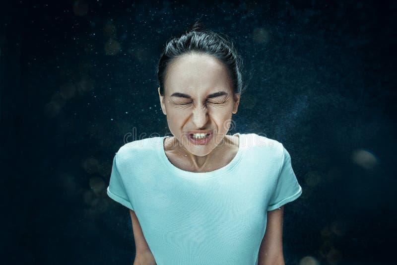 Jovem mulher que espirra, retrato do estúdio imagem de stock