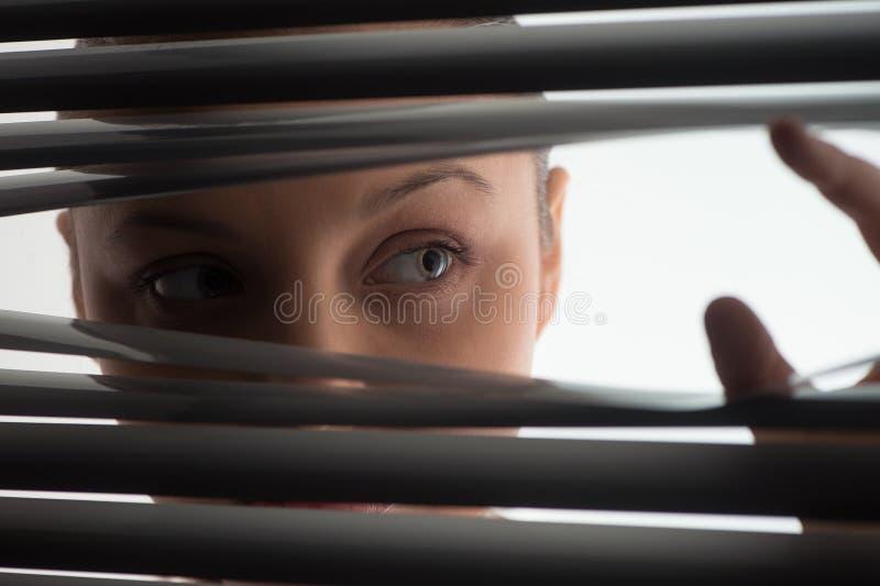 Jovem mulher que espreita através das cortinas fechados ou dos obturadores imagens de stock