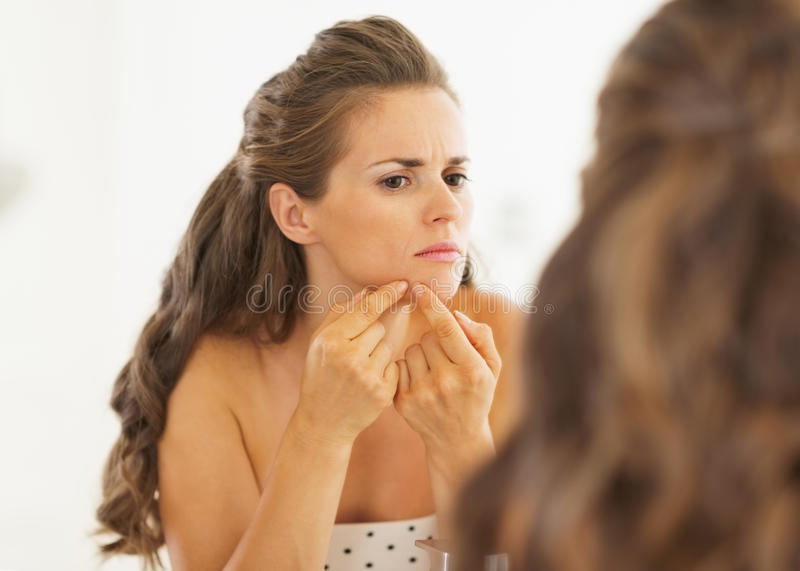 Jovem mulher que espreme a acne no banheiro imagens de stock royalty free