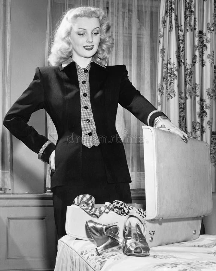 Jovem mulher que está ao lado de sua cama, sustentando a mala de viagem, pensando de que embalar (todas as pessoas descritas não  foto de stock royalty free