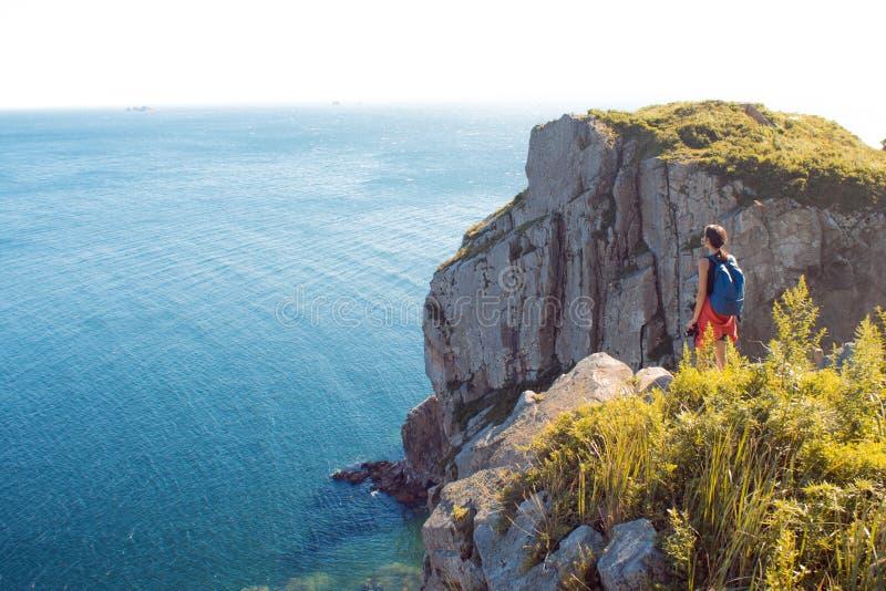 Jovem mulher que está apenas em um penhasco rochoso Turista da menina no fundo de animais selvagens, do mar e de rochas bonitos fotos de stock royalty free