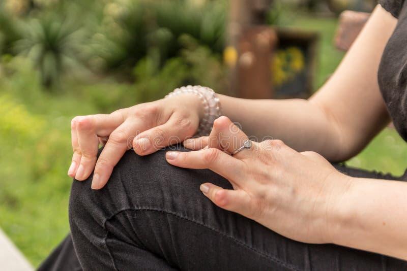 A jovem mulher que está com a artrite reumatoide toma um resto que senta-se em um banco em um parque As mãos e os pés são deforma imagem de stock royalty free