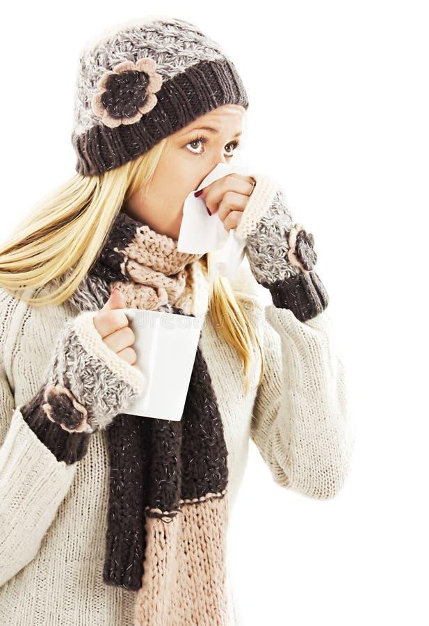 Jovem mulher que está com a gripe e que funde seu nariz no lenço foto de stock