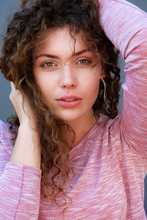 Jovem mulher que está com mãos no cabelo fotos de stock
