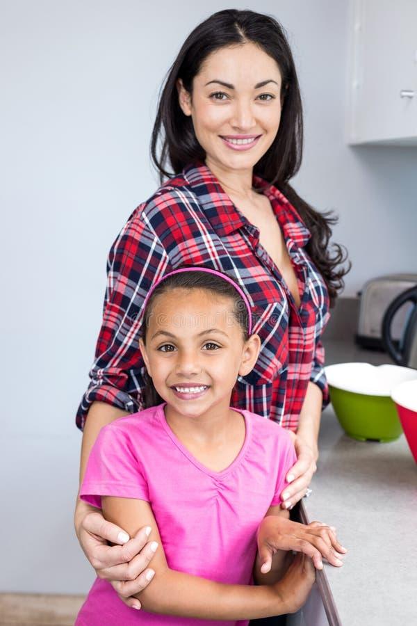 Jovem mulher que está com sua filha na cozinha imagens de stock royalty free