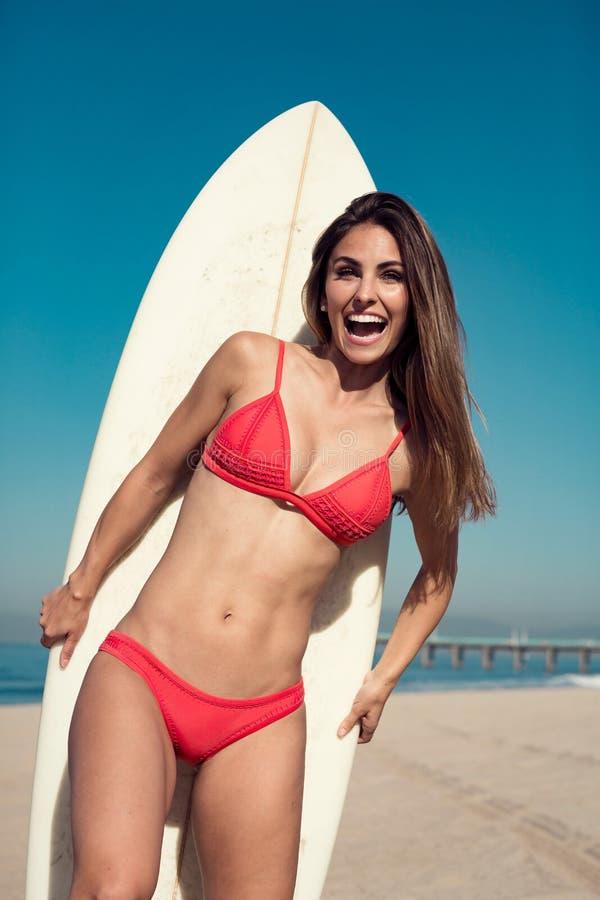 Jovem mulher que está com uma prancha na praia fotos de stock royalty free
