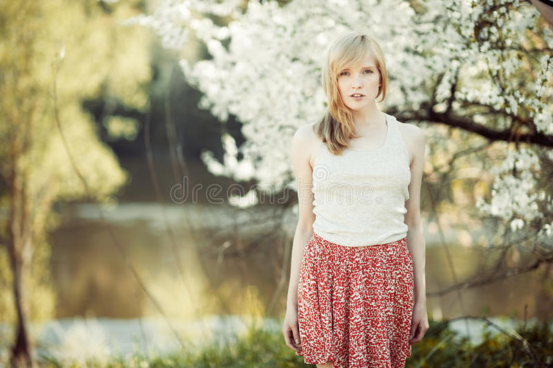 Jovem mulher que está em um parque do verão perto de um lago foto de stock