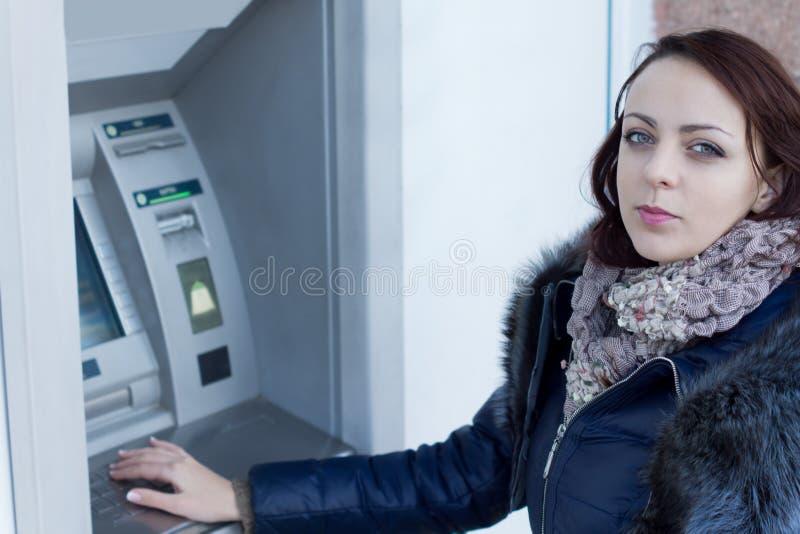 Jovem mulher que está em uma máquina do ATM foto de stock royalty free