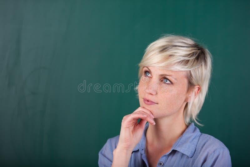 Jovem mulher que está na frente do quadro-negro imagens de stock royalty free
