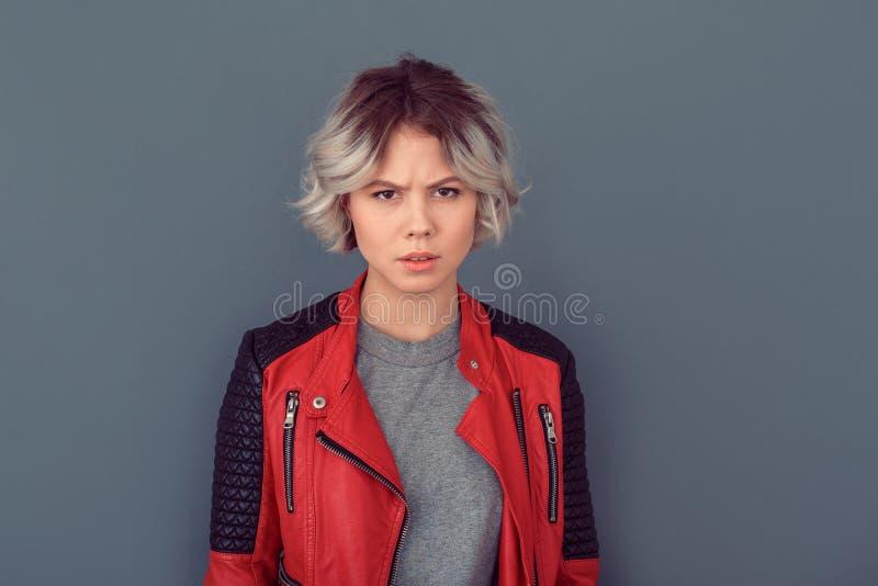 Jovem mulher que está no casaco de cabedal isolado na parede cinzenta irritada foto de stock