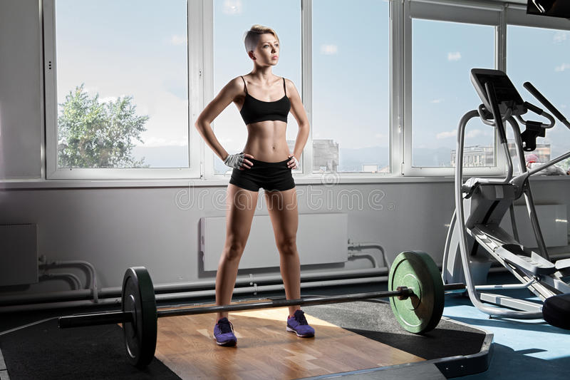 Jovem mulher que está no gym com os barbells no assoalho imagem de stock royalty free