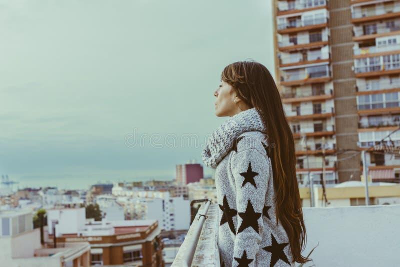 Jovem mulher que está no perfil no telhado, olhando a cidade, imagens de stock royalty free