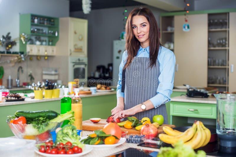 Jovem mulher que está no seu cozimento vestindo do avental da cozinha, cortando o fruto em uma placa fotos de stock