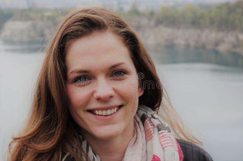 Jovem mulher que está pelo lago imagem de stock