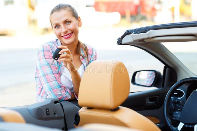 Jovem mulher que está perto de um convertible com chaves à disposição fotos de stock