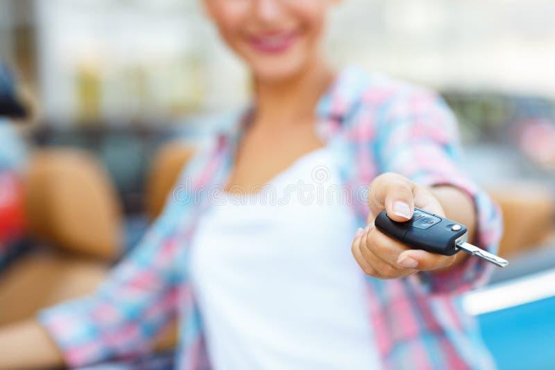 Jovem mulher que está perto de um convertible com chaves à disposição imagens de stock