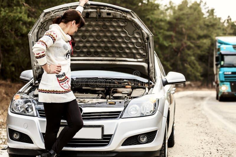 Jovem mulher que está perto do carro quebrado A menina abriu a capa e o olhar no motor Carro da mulher da reaparelhagem foto de stock royalty free