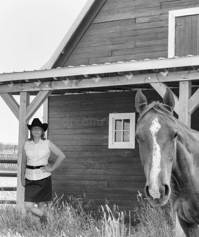 Jovem mulher que está por um celeiro com um cavalo no primeiro plano foto de stock