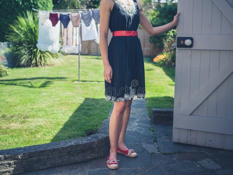 Jovem mulher que está por uma vertente no jardim foto de stock royalty free