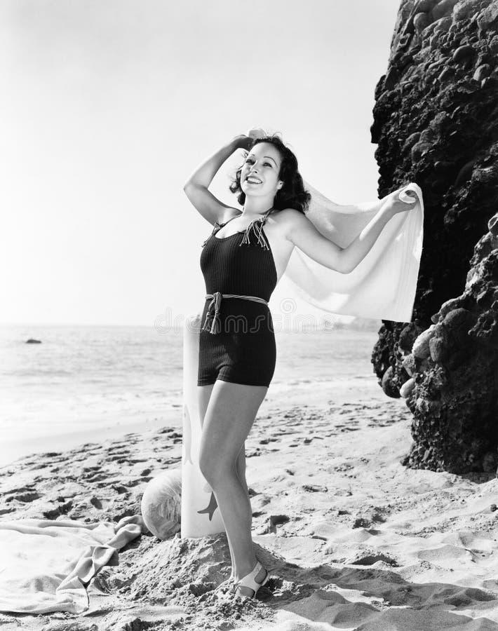 Jovem mulher que estão na praia e sorriso (todas as pessoas descritas não são umas vivas mais longo e nenhuma propriedade existe  imagens de stock