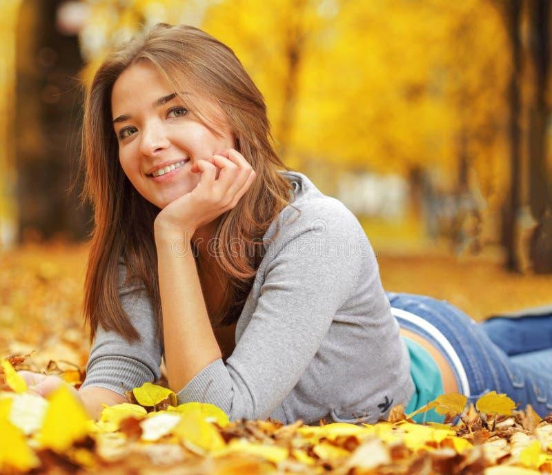 Jovem mulher que estabelece na terra em Autumn Park, menina da beleza na floresta da queda foto de stock
