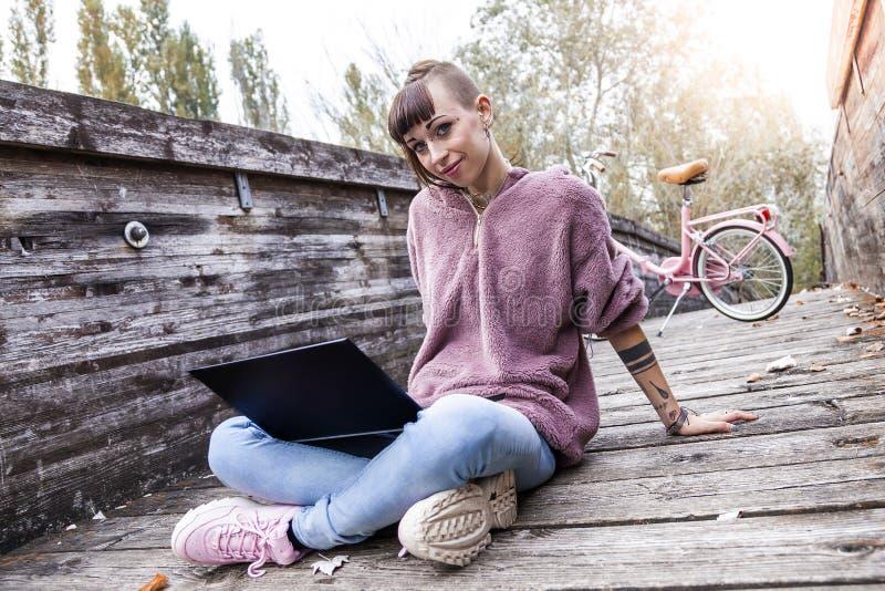 Jovem mulher que estuda com o computador que senta-se em uma ponte de madeira fotos de stock royalty free