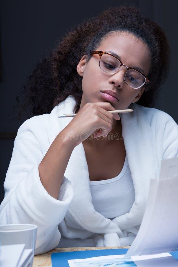 Jovem mulher que estuda na noite imagens de stock