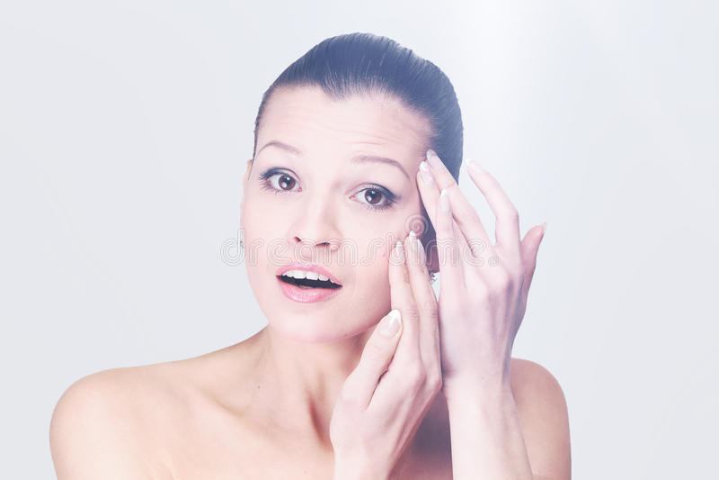Jovem mulher que examina seus cara e enrugamentos que podem aparecer, iso imagens de stock royalty free