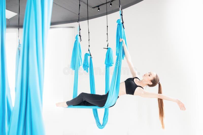 Jovem mulher que executa o exercício aéreo antigravitante da ioga no estúdio branco Meditação do conceito foto de stock