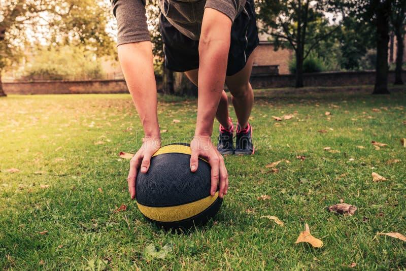 Jovem mulher que exercita com a bola de medicina no parque imagem de stock