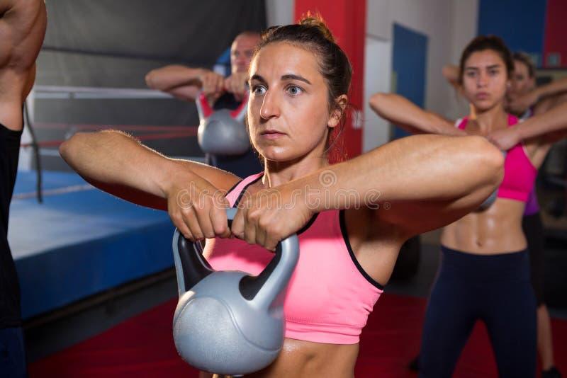 Jovem mulher que exercita com a chaleira contra atletas imagem de stock royalty free