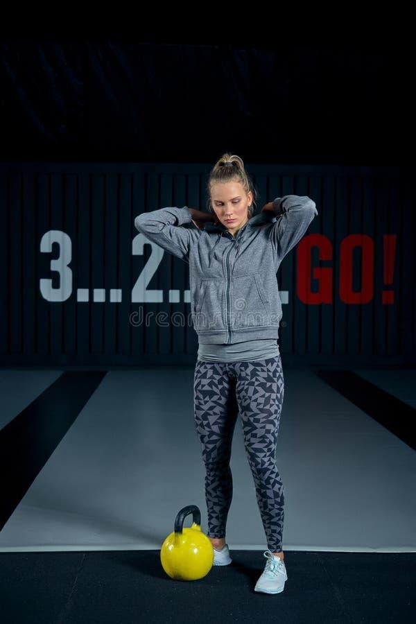 Jovem mulher que exercita com kettlebells no gym Ocupas que squatting o gym da aptidão do balanço WOD Exercício da mulher da apti fotos de stock