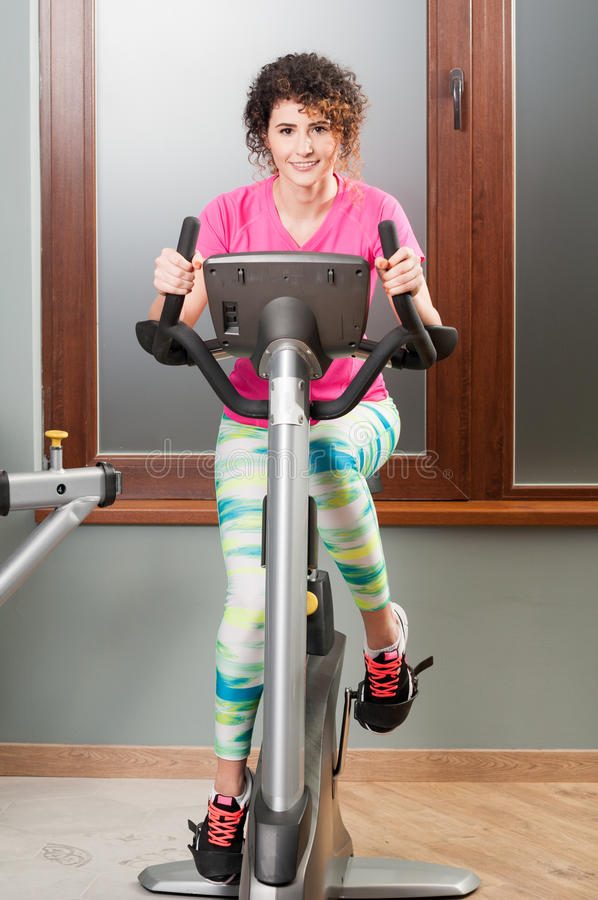 Jovem mulher que exercita e que treina na bicicleta fotografia de stock