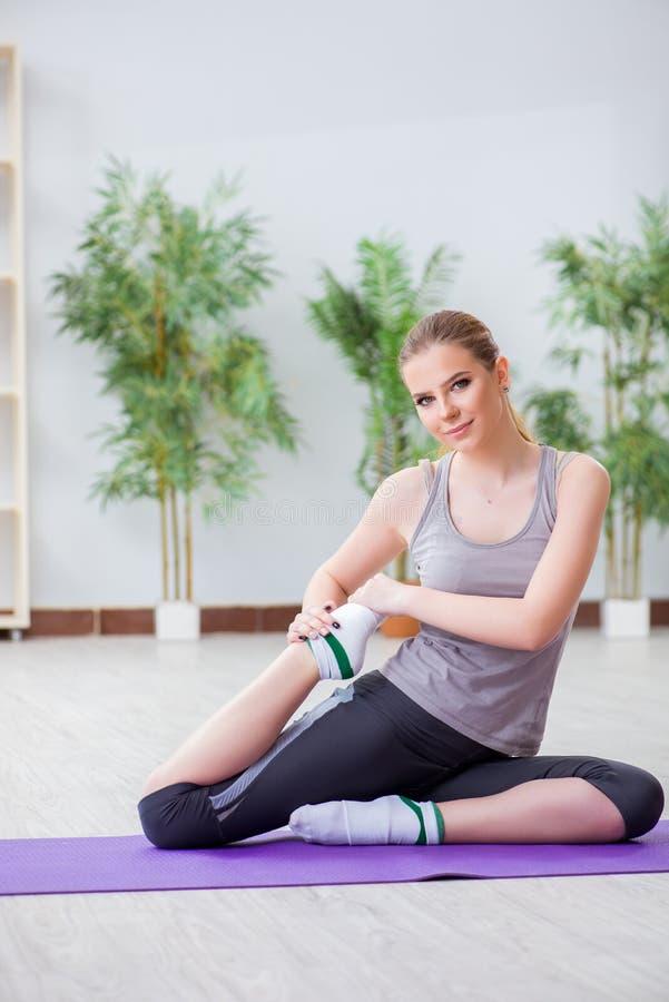 A jovem mulher que exercita no salão de esportes no conceito saudável imagens de stock royalty free
