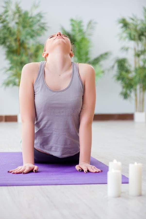A jovem mulher que exercita no salão de esportes no conceito saudável imagens de stock