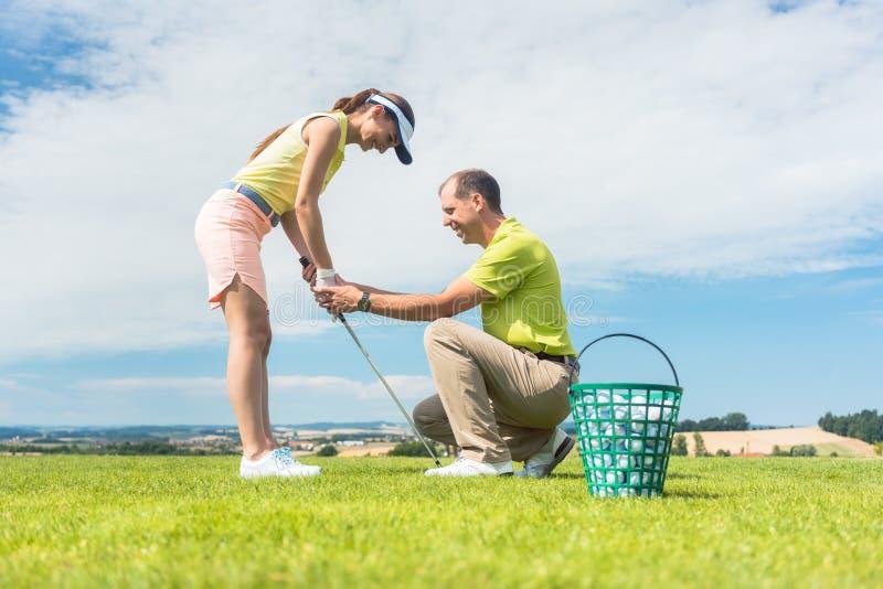 A jovem mulher que exercita o balanço do golfe ajudou por seu instrutor imagens de stock