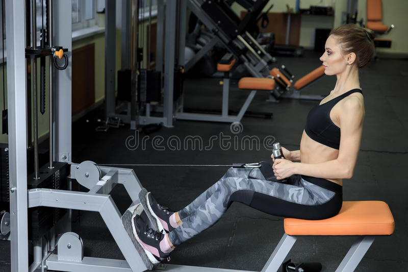 Jovem mulher que exercita para trás na máquina no Gym e que dobra os músculos - modelo atlético muscular da aptidão do halterofil fotografia de stock