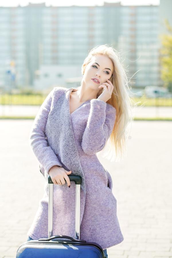 Jovem mulher que fala em um telefone celular na rua suitcase E fotos de stock royalty free