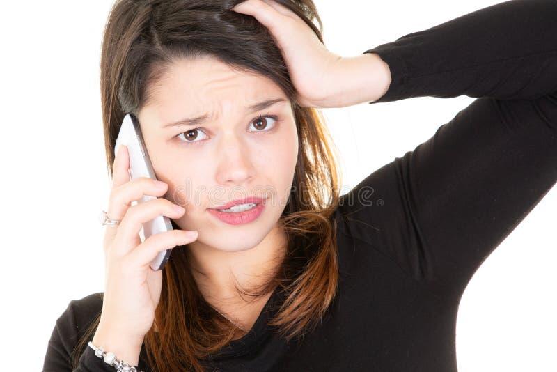 Jovem mulher que fala na raiva muito emocional do telefone em um fundo branco fotografia de stock