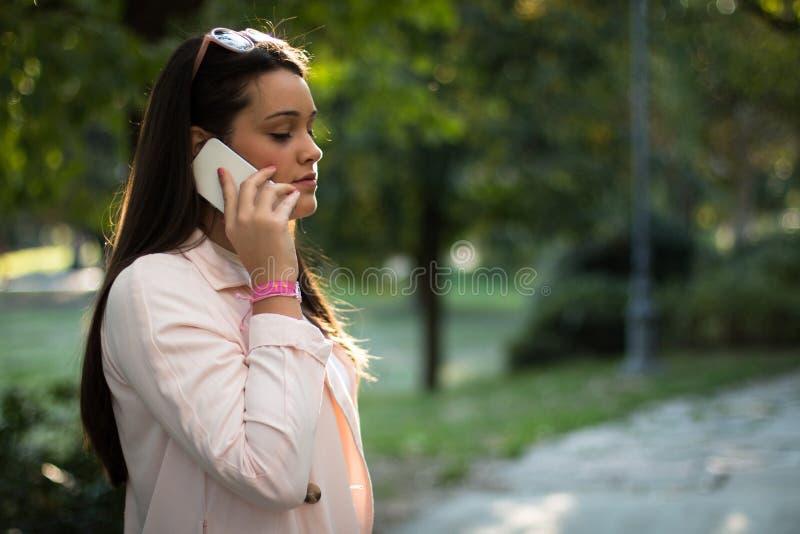 Jovem mulher que fala no smartphone seriamente fora no parque imagem de stock royalty free