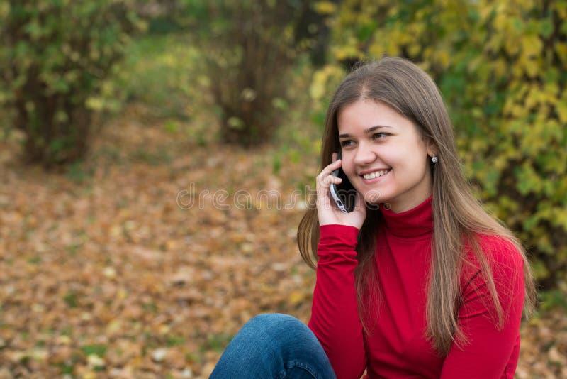 Jovem mulher que fala no telefone celular na queda fotografia de stock royalty free