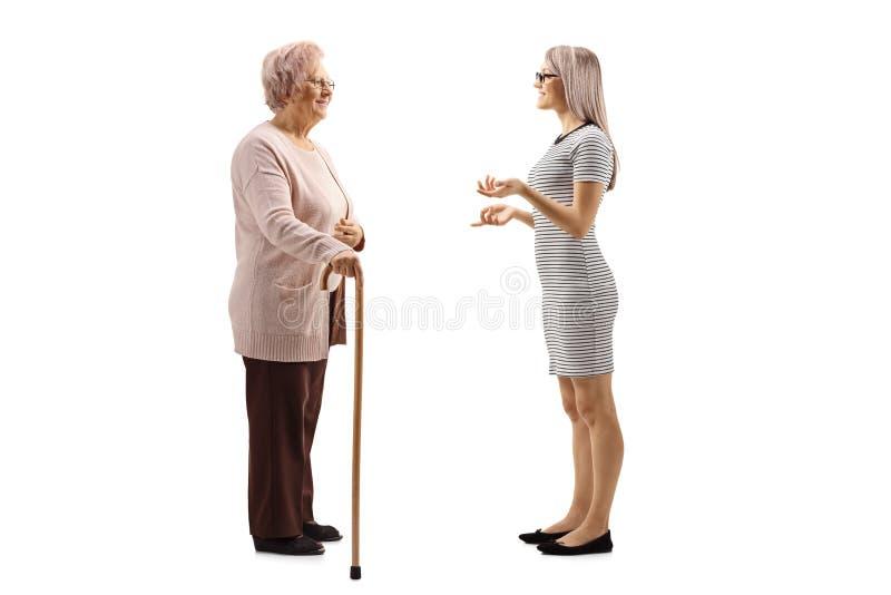Jovem mulher que fala a uma mulher superior com um bastão fotografia de stock