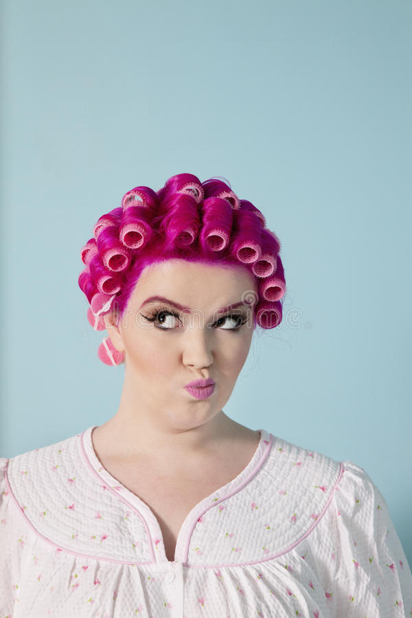 Jovem mulher que faz as caras com cabelo e os encrespadores cor-de-rosa sobre o fundo colorido imagens de stock