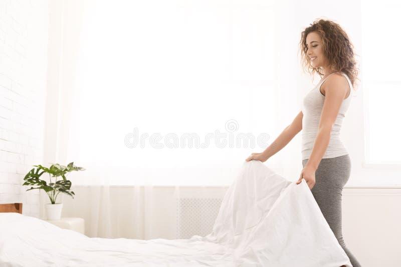 Jovem mulher que faz a cama e que organiza a sala foto de stock