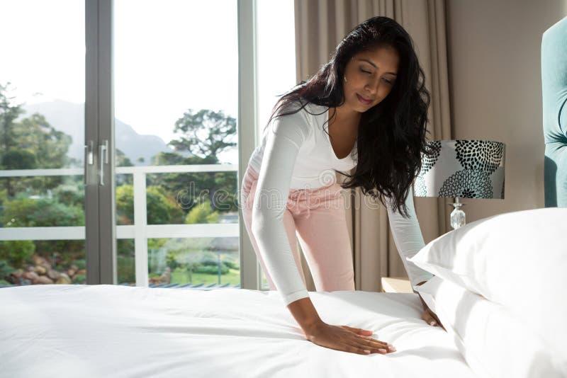 Jovem mulher que faz a cama em casa fotos de stock