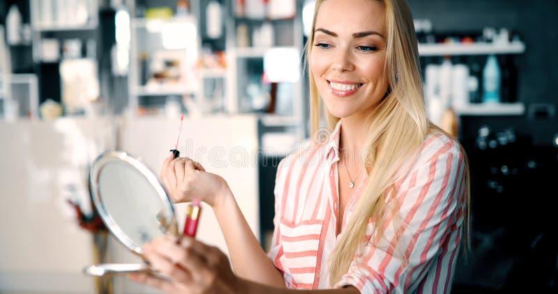 Jovem mulher que faz a composição perto do espelho imagens de stock royalty free